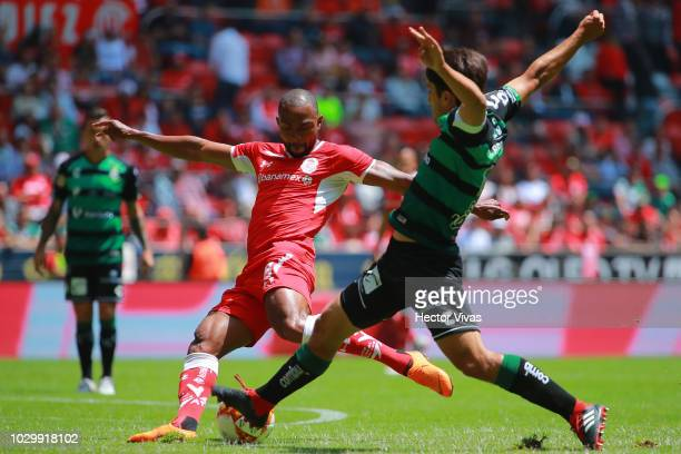 William Da Silva of Toluca kicks the ball to score the first goal of his team against Jose Abella of Santos Laguna during the 8th round match between...