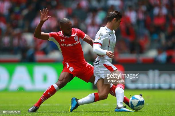 William Da Silva of Toluca struggles for the ball with Isaac Brizuela of Chivas during the third round match between Toluca and Chivas as part of the...