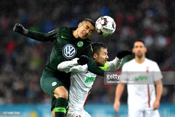 William de Asevedo Furtado of VfL Wolfsburg wins a header over Daniel Baier of Augsburg during the Bundesliga match between FC Augsburg and VfL...