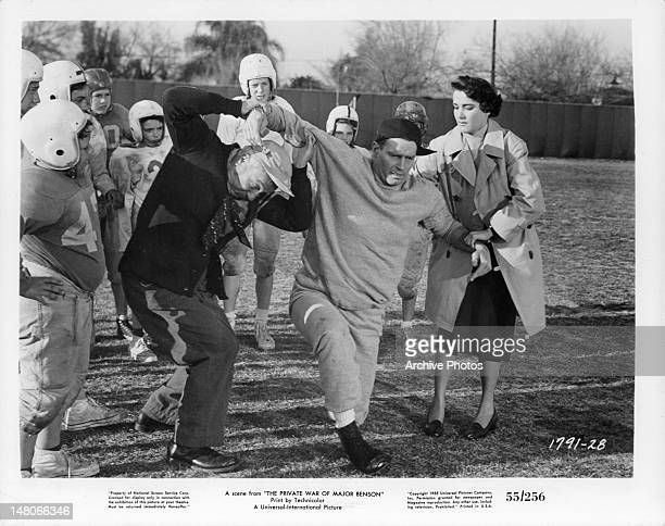 William Demarest helping injured Charlton Heston off the field with Julie Adams nearby in a scene from the film 'The Private War Of Major Benson' 1955