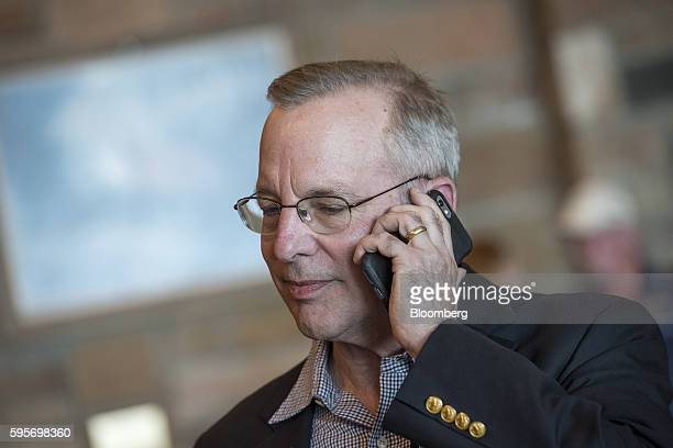 William Dudley president and chief executive officer of the Federal Reserve Bank of New York uses a smartphone as he arrives for a welcome dinner...