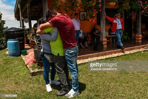 William Duque Escobar's former gardener is comforted by his son and wife during an eviction procedure at La Manuela a former vacation estate of late...