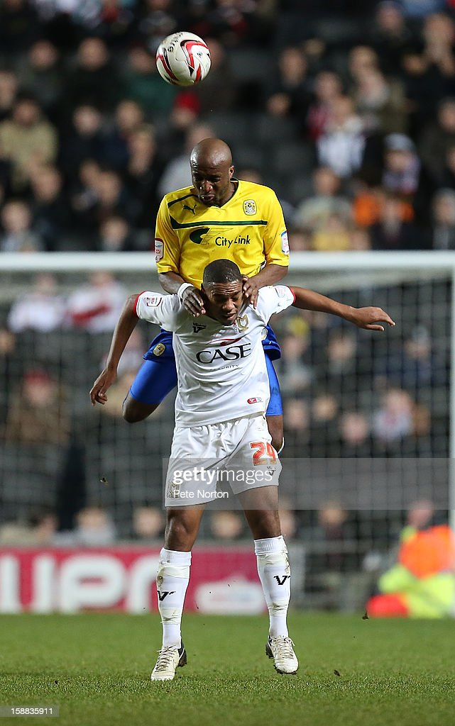 William Edjenguele of Coventry City rises above Angelo Balanta of Milton Keynes Dons to head the ball during the npower League One match between Milton Keynes Dons and Coventry City at Stadium mk on December 29, 2012 in Milton Keynes, England.