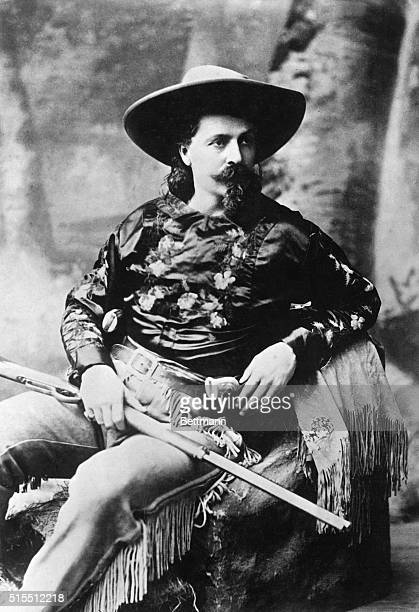 William Frederick 'Buffalo Bill' Cody American scout and showman seated in fringed pants gun belt floral print shirt and hat Undated photograph