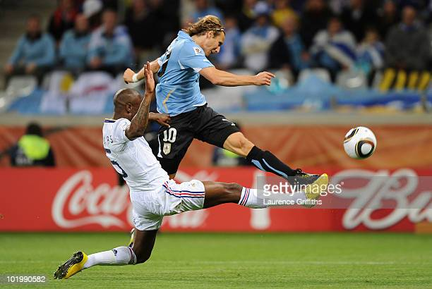 William Gallas of France defends a shot from Diego Forlan of Uruguay during the 2010 FIFA World Cup South Africa Group A match between Uruguay and...