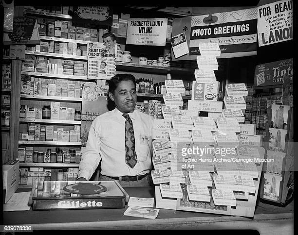 William Goode wearing shirt with pens in left breast pocket standing behind counter in his Goode Pharmacy with signs reading 'Parquette Luxury...