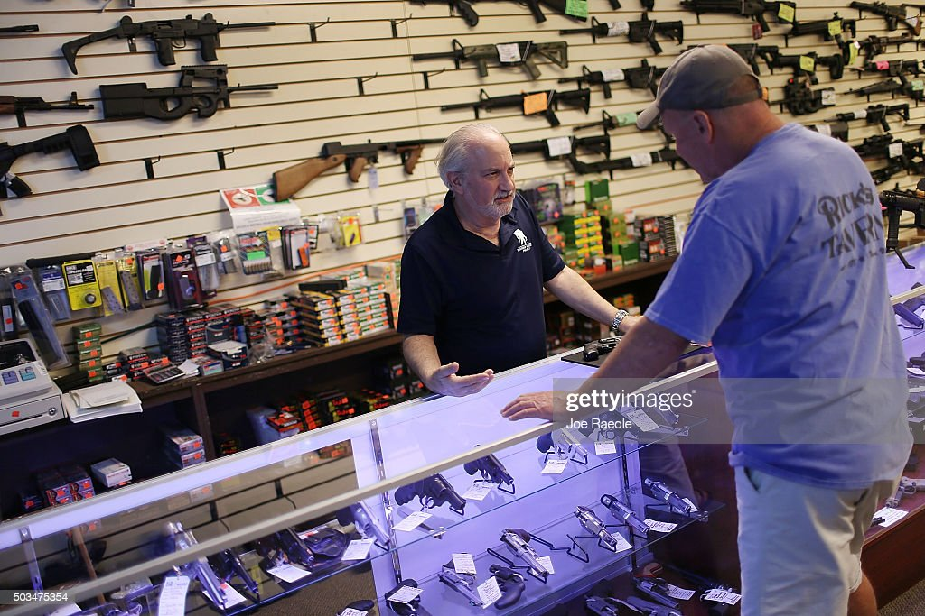 William Gordon, (L), helps Mark O'Connor as he shops for a handgun at the K&W Gunworks store on the day that U.S. President Barack Obama in Washington, DC announced his executive action on guns on January 5, 2016 in Delray Beach, Florida. President Obama announced several measures that he says are intended to advance his gun safety agenda.