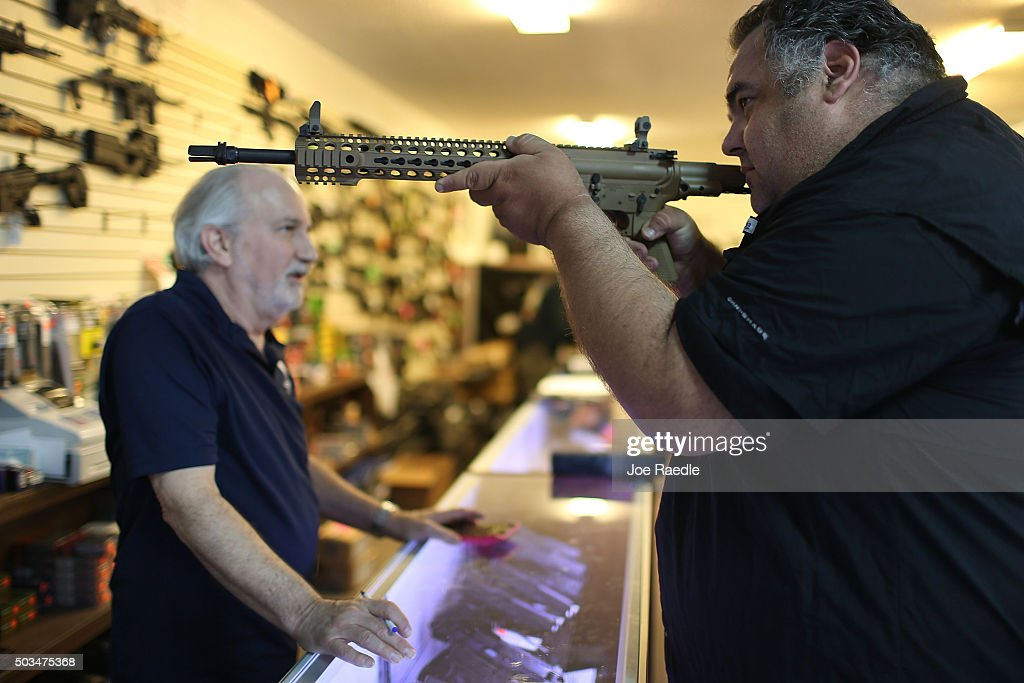 William Gordon, (L), helps Steve Wrona as he looks at weapons while visiting the K&W Gunworks store on the day that U.S. President Barack Obama in Washington, DC announced his executive action on guns on January 5, 2016 in Delray Beach, Florida. President Obama announced several measures that he says are intended to advance his gun safety agenda.