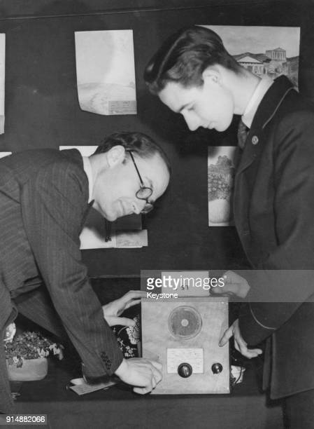William Hare 5th Earl of Listowel the PostmasterGeneral listens to a wireless set made by 15yearold A J E Chapman after opening a Handicraft...