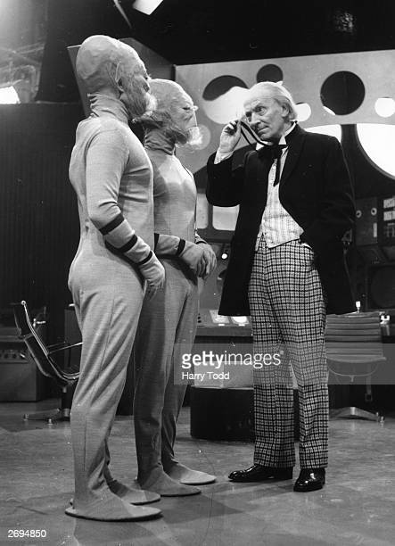 William Hartnell as Dr Who peers through his monocle at two extraterrestrials during filming of the popular science fiction series 'Dr Who' at the...