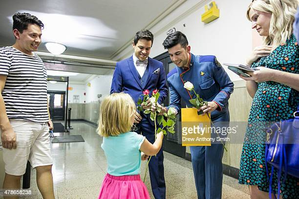 William Hensel takes a rose from Finley Wilson at the Travis County Courthouse after signing a marriage certificate with his spouse Justin Ables on...