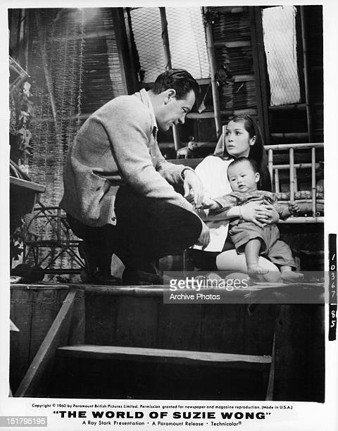 William Holden and Nancy Kwan with a baby in a scene from the film 'The World Of Suzie Wong' 1960