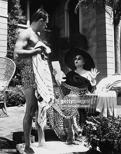 William Holden as Joe Gillis and Gloria Swanson as Norma Desmond talk by the pool during the filming of the 1950 film Sunset Boulevard