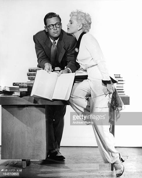 William Holden puts down a book as he is distracted by Judy Holliday in a promotional portrait for the film 'Born Yesterday' 1950