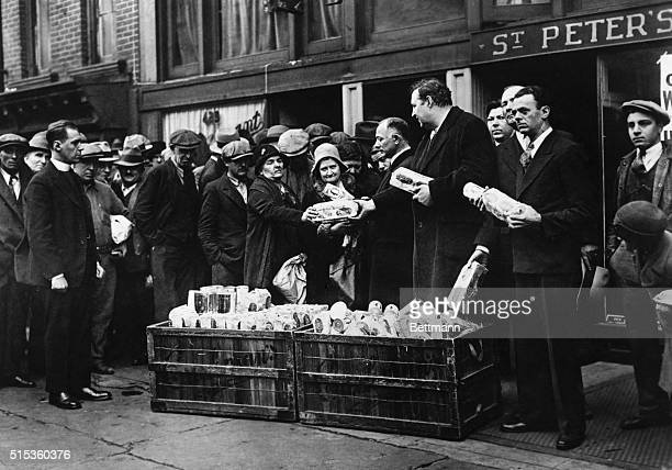 William I Sirovich and Heywood Brown shown above with the Reverend Raymond Norman are dealing out bread and coffee to hungry and jobless at St...