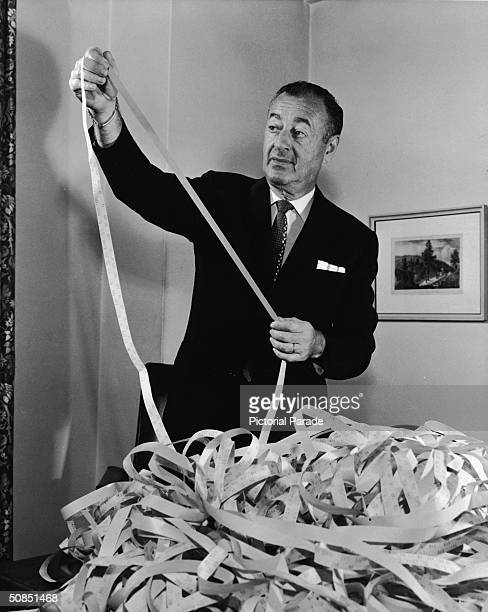 William J Levitt president of Levitt and Sons Inc reads ticker tape as trading in his firm's stock begins on the American Stock Exchange July 8 1963...