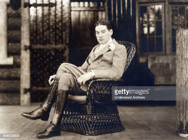 William K Vanderbilt sits in a wicker chair wearing riding boots and carnation in his lapel, circa 1887.