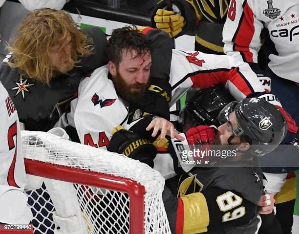 William Karlsson of the Vegas Golden Knights grabs Brooks Orpik of the Washington Capitals as he hits Alex Tuch of the Golden Knights after a...