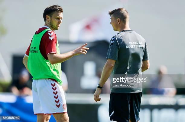 William Kvist speaks to Jon Dahl Tomasson assistant coach of Denmark during the Denmark training session at Helsingor Stadion on August 29 2017 in...