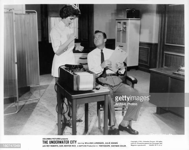 William Lundigan looking up at Julie Adams in a scene from the film 'The Underwater City' 1961