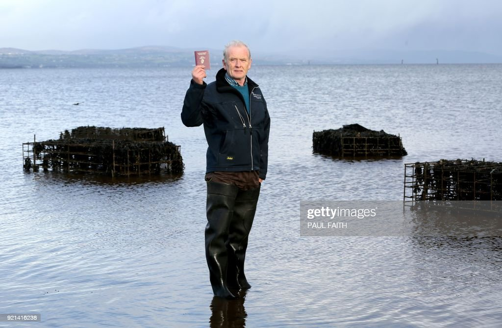 William Lynch, an oyster farmer, poses with his Irish passport at his Culmore point farm, in Lough Foyle Northern Ireland, beside the Donegal border of the Irish Republic, on January 15, 2018. On Brexit he says: 'A hard border would be totally impossible for me with a Northern Ireland company. There would be tariffs shipping the same oysters out. I will close down the business and open a company in southern Ireland.' A sheep farmer, a stockbroker, a radio presenter: AFP spoke to 15 people across Europe whose careers are already deeply impacted by Brexit more than a year before Britain's departure date.