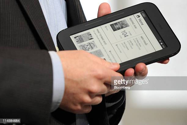 William Lynch chief executive officer of Barnes Noble Inc displays the new Nook electronic reader during an event in New York US on Tuesday May 24...
