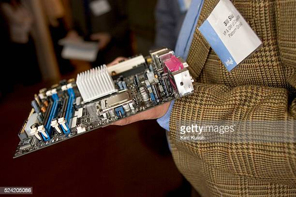 William M Siu vice president general manager Desktop Platforms Group Intel Corp displays a motherboard with their newest chipset codenamed Grantsdale...