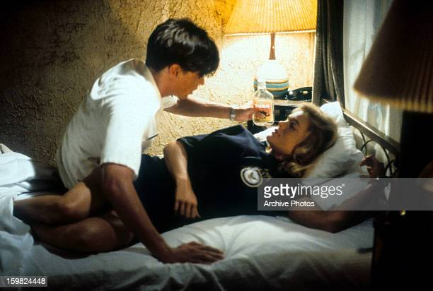 William McNamara leaning over Erika Eleniak in bed in a scene from the film 'Chasers' 1994
