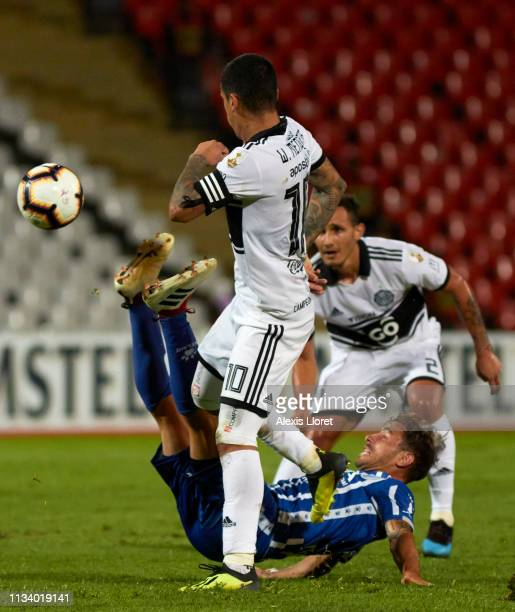 William Mendieta and Willian Candia of Club Olimpia compete for the ball with Hernan Bernardello of Godoy Cruz during a group C match between Godoy...