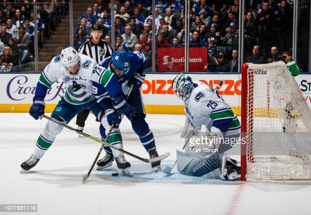 William Nylander of the Toronto Maple Leafs battles for the puck against Alexander Edler of the Vancouver Canucks in front of Jacob Markstrom during...