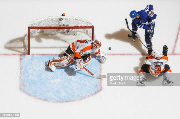 William Nylander of the Toronto Maple Leafs goes to the net against Brian Elliott and Radko Gudas of the Philadelphia Flyers during the third period...