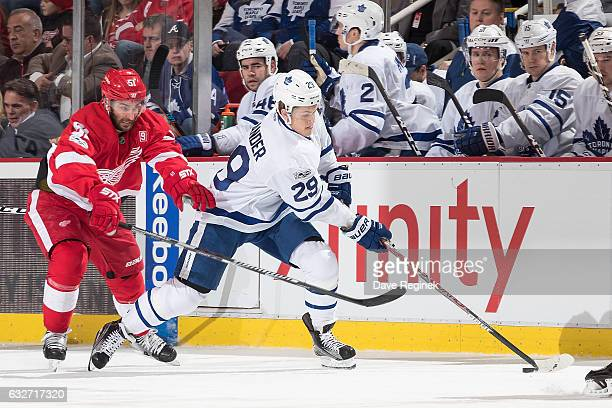 William Nylander of the Toronto Maple Leafs skates up ice with the puck followed by Frans Nielsen of the Detroit Red Wings during an NHL game at Joe...