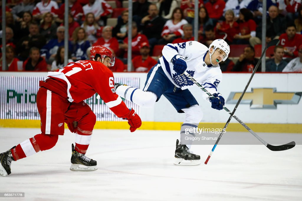 William Nylander #29 of the Toronto Maple Leafs takes a third period shot past the flying stick of Xavier Ouellet #61 of the Detroit Red Wings at Joe Louis Arena on April 1, 2017 in Detroit, Michigan. Toronto won the game 5-4.