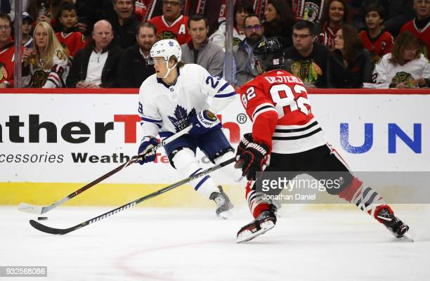 William Nylander of the Toronto Maple Leafs turns with the puck next to Jordan Oesterle of the Chicago Blackhawks at the United Center on January 24...