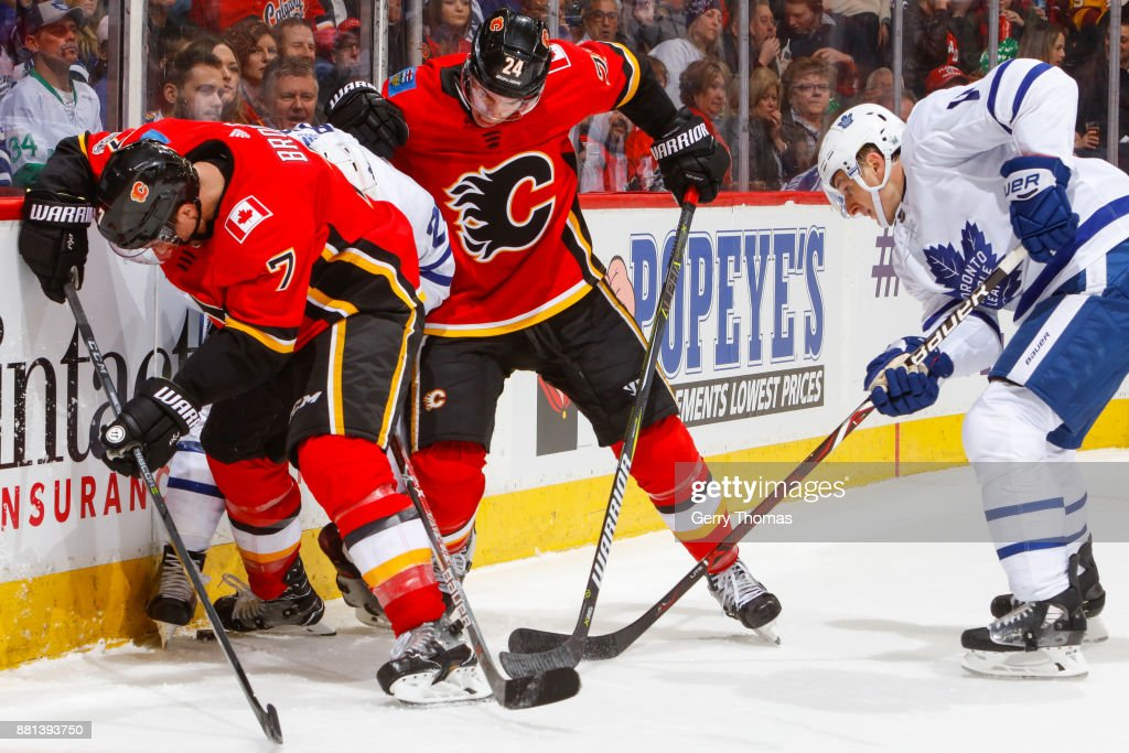 William Nylander #29, Zach Hyman #11 of the Toronto Maple Leafs, TJ Brodie #7 and Travis Hamonic #24 of the Calgary Flames battle for the puck in an NHL game against the Toronto Maple Leafs at the Scotiabank Saddledome on November 28, 2017 in Calgary, Alberta, Canada.