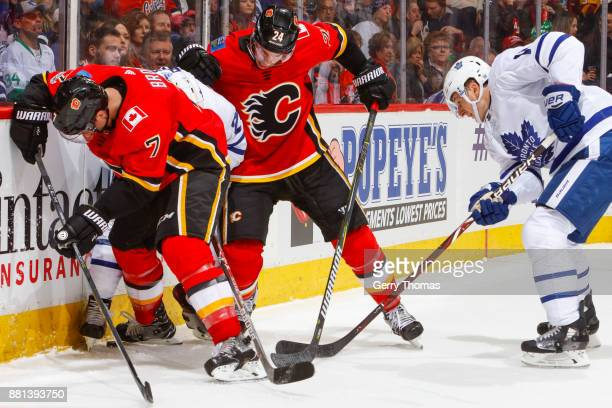 William Nylander Zach Hyman of the Toronto Maple Leafs TJ Brodie and Travis Hamonic of the Calgary Flames battle for the puck in an NHL game against...