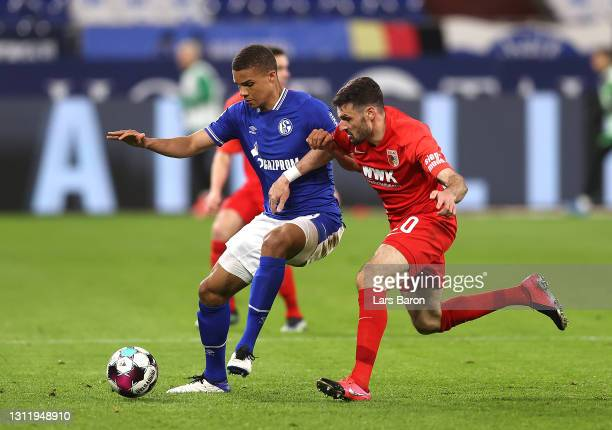 William of FC Schalke 04 battles for possession with Daniel Caligiuri of FC Augsburg during the Bundesliga match between FC Schalke 04 and FC...