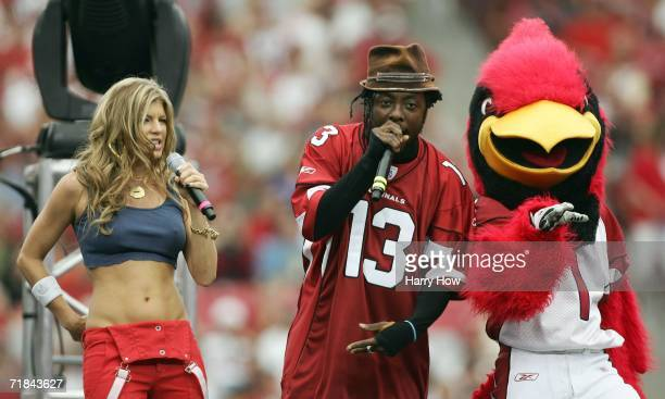 William of the Black Eyed Peas sings while wearing a Kurt Warner's jersey along with Fergie and the Cardinals mascot Big Red in the pregame show in...