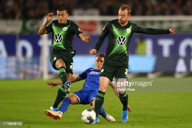 William of VfL Wolfsburg and Maximilian Arnold of VfL Wolfsburg battles for possession with Dennis Geiger of TSG 1899 Hoffenheim during the...