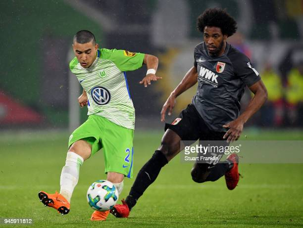 William of Wolfsburg and Caiuby of Augsburg battle for the ball during the Bundesliga match between VfL Wolfsburg and FC Augsburg at Volkswagen Arena...
