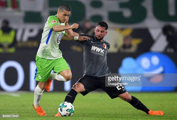 William of Wolfsburg and Marco Richter of Augsburg battle for the ball during the Bundesliga match between VfL Wolfsburg and FC Augsburg at...