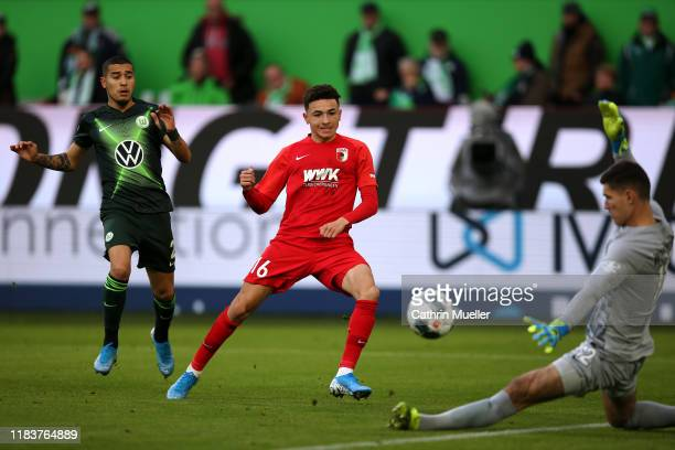 William of Wolfsburg battles for the ball with Ruben Vargas of Augsburg as he shoots on goal at Goalkeeper, Pavao Pervan of Wolfsburg during the...