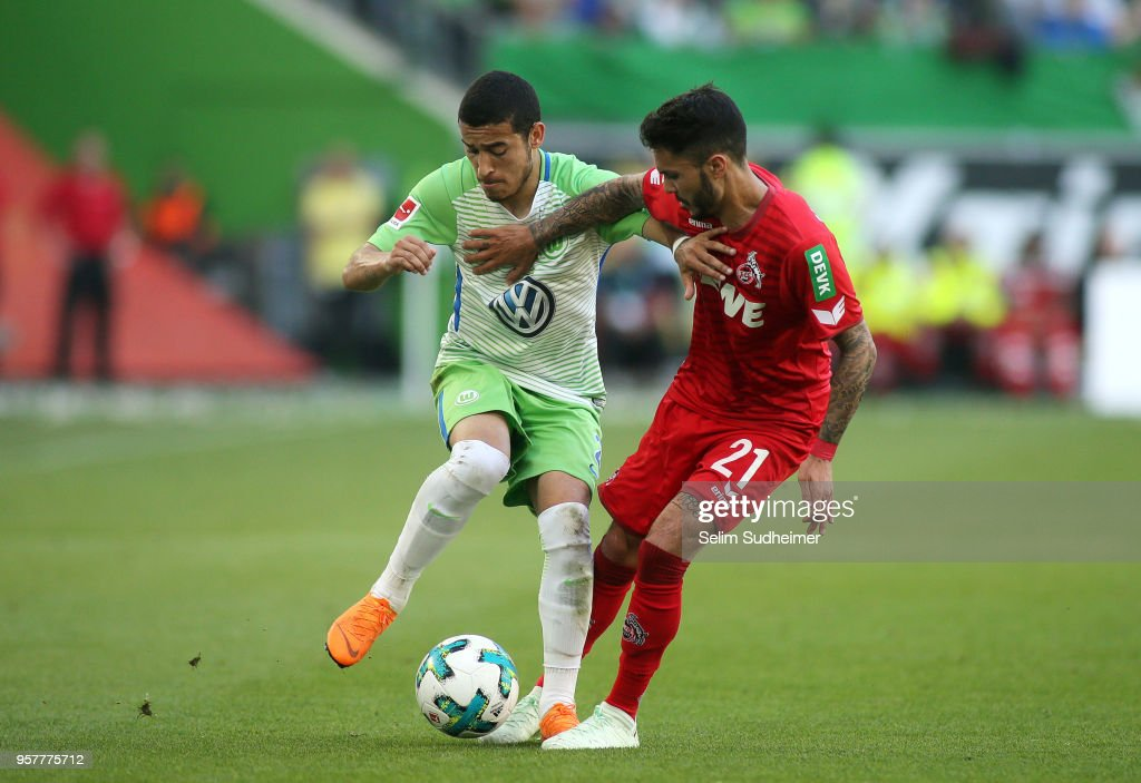 William of Wolfsburg (L) fights for the ball with Leonardo Bittencourt of Koeln reacts during the Bundesliga match between VfL Wolfsburg and 1. FC Koeln at Volkswagen Arena on May 12, 2018 in Wolfsburg, Germany.