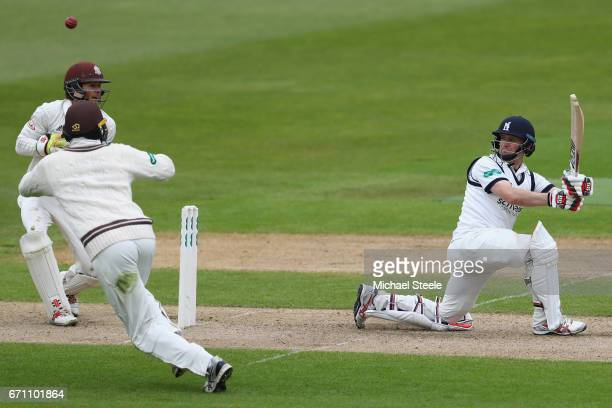 William Portefield of Warwickshire scoops a shot to the legside as wicketkeeper Ben Foakes of Surrey looks on during day one of the Specsavers County...