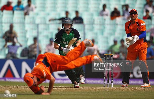 William Porterfield of Ireland hits the ball past Peter Borren of the Netherlands as Atse Buurman looks on during the 2011 ICC World Cup match...