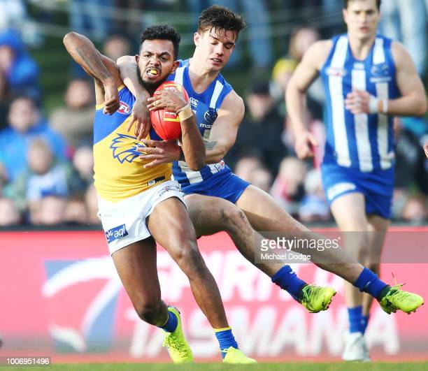 William Rioli of the Eagles is tackled high by Jy Simkin of the Kangaroos but received no free kick during the round 19 AFL match between the North...