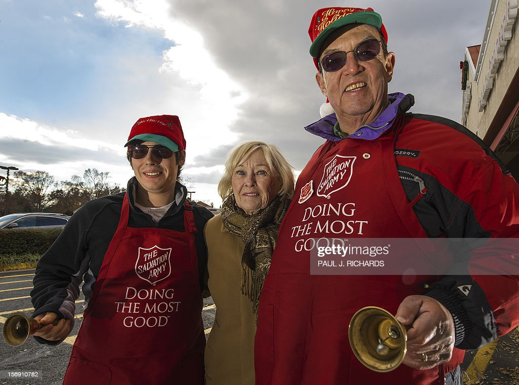 William Schmidt (R), and his grandson Bubba Wellens (L) pose for a photo when Schmidt's wife, Pat (C) shows up to check on her volunter family working in the cold at a Salvation Army donation kettle outside a Giant grocery store November 24, 2012, in Clifton, Virgina. Bell ringers William Schmidt, who has worked as a volunteer for 20 years at this store, and his grandson Bubba Wellens volunteer for the Salvation Army to collect donations from holiday shoppers for the needy between Thanksgiving and Christmas. Schmidt does it all 'to teach others the joy of giving'. AFP Photo/Paul J. Richards