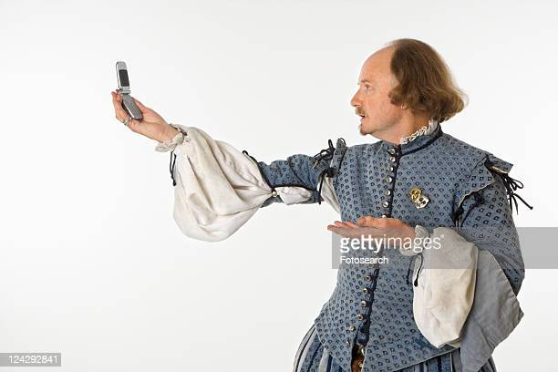 William Shakespeare in period clothing holding cell phone and gesturing.
