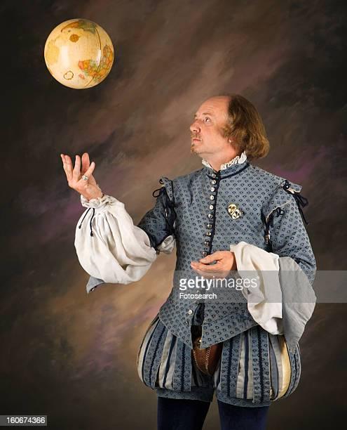 william shakespeare in period clothing tossing globe into air - renaissance stock-fotos und bilder