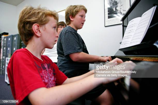 William Shannon left and his brother Jackson practice the piano as their teacher Brenda diZerega watches at Saint Stephen's Episcopal Church Friday...
